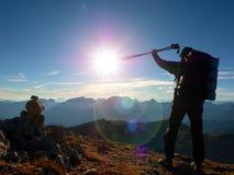 Het tekort van de lensgloed al backpacker met in hand polen Zonnig weer in rotsachtige bergen stock afbeelding