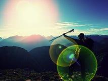 Het tekort van de lensgloed al backpacker met in hand polen Zonnig weer in rotsachtige bergen stock foto's