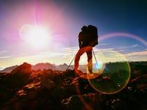 Het tekort van de lensgloed Mensenwandelaar met rugzakgang op rotsachtige piek Mens die o loopt stock afbeeldingen