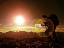 Het tekort van de lensgloed Mensenwandelaar met rugzakgang op rotsachtige piek Mens die o loopt stock foto's
