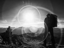Het tekort van de lensgloed Silhouet van de mens met hodd, rugzak en polen ter beschikking Mensengang stock foto's