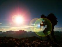 Het tekort van de lensgloed Silhouet van de mens met kap, rugzak en polen ter beschikking Mensengang stock foto