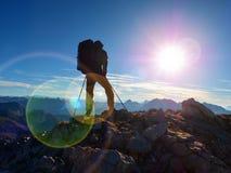 Het tekort van de lensgloed Silhouet van de mens met kap, rugzak en polen ter beschikking Mensengang stock afbeelding