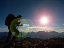 Het tekort van de lensgloed Toeristengids op trekkingsweg met polen en rugzak Ervaren wandelaar royalty-vrije stock fotografie