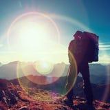 Het tekort van de lensgloed Toeristengids op trekkingsweg met polen en rugzak Ervaren wandelaar stock foto's