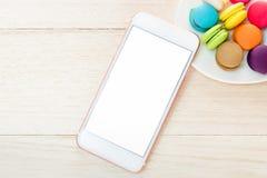 Het telefoon witte scherm op de lijst met makarons in de plaat nabijgelegen Royalty-vrije Stock Afbeelding