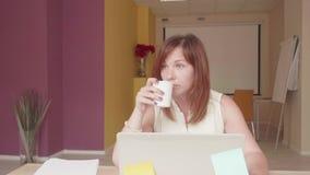 Het teleurgestelde meisje zit voor laptop, schrijft ongeveer en werpt document stock video