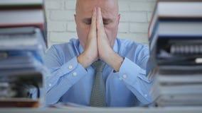 Het teleurgestelde Verblijf van Zakenmanin office room met dient in bidt Gebaren royalty-vrije stock foto
