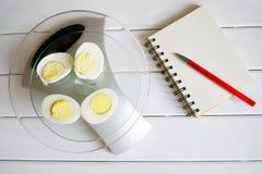 Het tellen van de hoeveelheid proteïne, calorieën, koolhydraten en vetten in voedsel Kippenei op de keukenschalen royalty-vrije stock foto's
