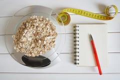 Het tellen van en het registreren van de hoeveelheid koolhydraten, calorieën, proteïnen en vetten in voedsel Vlokken van vier gra stock foto