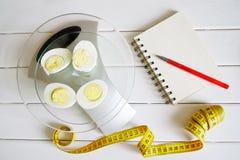 Het tellen van en het registreren van de hoeveelheid proteïne, calorieën, koolhydraten en vetten in voedsel Kippenei op de keuken stock foto's