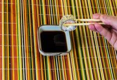 Het Tempurabroodje met zalm houdt een hand tegen de achtergrond van een veelkleurige bamboedoek royalty-vrije stock fotografie
