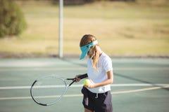 Het tennisbal en racket van de meisjesholding op hof Royalty-vrije Stock Afbeelding