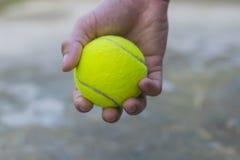 Het tennisbal van de mensenholding Stock Foto