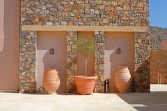De muur van de steen met de potten van het boomterracotta (Griekenland) Stock Foto's