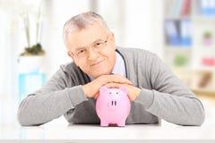 Het tevreden heer stellen over een spaarvarken bij zijn huis Royalty-vrije Stock Fotografie