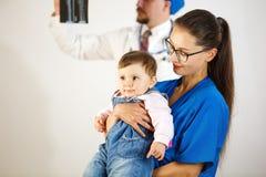 Het tevreden kind in de wapens van een arts, op de achtergrond de arts bekijkt een röntgenstraal Witte achtergrond stock afbeelding