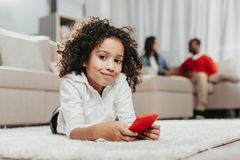 Het tevreden kind ontspannen op deken met smartphone royalty-vrije stock afbeelding