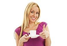 Het tevreden meisje geniet van drinkend haar koffie en tonend duimen Royalty-vrije Stock Afbeeldingen