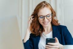 Het tevreden rode haired vrouwelijke gebruiks moderne elektronische apparaat om te controleren newsfeed, online mededeling en het royalty-vrije stock afbeelding