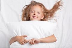 Het tevreden speelse meisje met charmante glimlach, omhelst hoofdkussen, ligt op wit hoofdkussen, heeft goede rust, geniet van we stock fotografie