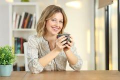 Het tevreden vrouw stellen die u thuis bekijken royalty-vrije stock foto