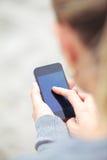 Het texting van de vrouw op een mobiele telefoon Royalty-vrije Stock Afbeeldingen