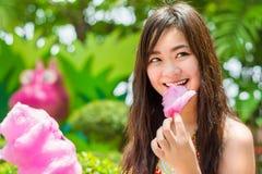 Het Thaise meisje eet roze candyfloss met vreugde royalty-vrije stock afbeelding
