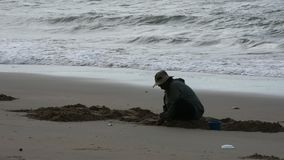 Het Thaise oude het gebruiksgietlepel van vrouwenmensen graven vindt shell en schaaldieren op het strand stock video