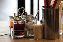 Het Thaise stijlkruiden, de vissensaus, suiker, azijn en Spaanse peper het poeder in glazen en het aluminium behandelen op houten Stock Foto