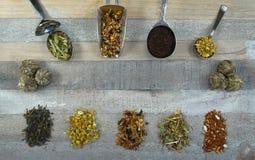 Het theeassortiment bij lepels en de losse thee met thee bloeien bij houten middel tegen oxidatie als achtergrond royalty-vrije stock foto's