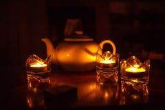 Het theestel op een donker licht als achtergrond en kaars is een concept traditionele Britse thee stock afbeelding