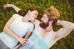 Het thema is sport en een gezonde levensstijl Een jonge man en vrouwenpaar rust het liggen op hun ruggen op het groene gras, een  royalty-vrije stock fotografie
