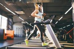 Het thema is sport en muziek Een mooie opgeblazen vrouwenlooppas in de gymnastiek op een tredmolen Op hoofd haar zijn grote witte stock foto