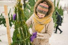 Het thema is het symbool van Kerstmis en Nieuwjaarvakantie De mooie jonge Kaukasische vrouwelijke klant, kiest, maakt een aankoop stock afbeelding