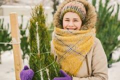 Het thema is het symbool van Kerstmis en Nieuwjaarvakantie De mooie jonge Kaukasische vrouwelijke klant, kiest, maakt een aankoop stock afbeeldingen