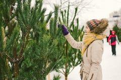 Het thema is het symbool van Kerstmis en Nieuwjaarvakantie De mooie jonge Kaukasische vrouwelijke klant, kiest, maakt een aankoop royalty-vrije stock fotografie