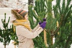 Het thema is het symbool van Kerstmis en Nieuwjaarvakantie De mooie jonge Kaukasische vrouwelijke klant, kiest, maakt een aankoop stock foto's