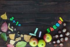 Het thema van de school De herfstbladeren, kastanjes en rijpe appelen op een donkere houten achtergrond Aan boord van de plaats v Stock Afbeelding