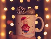 Het thema van Kerstmis in de hand van een mok met een varken en Kerstmisballen Bokeh op de achtergrond Het fonkelen lichten op de royalty-vrije stock foto