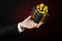 Het thema van vieringen en giften: een mens in een zwart kostuum die een exclusieve die gift houden in een zwarte doos met gouden Stock Foto