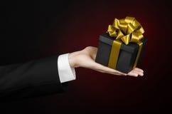 Het thema van vieringen en giften: een mens in een zwart kostuum die een exclusieve die gift houden in een zwarte doos met gouden Royalty-vrije Stock Afbeeldingen
