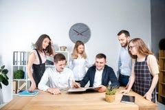 Het thema is zaken en groepswerk Een groep jonge Kaukasische mensenbeambten die een vergadering, briefing houden, die met documen stock fotografie