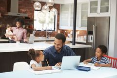 Het Thuiswerk van vaderhelps children with terwijl de Moeder met Baby Laptop in Keuken gebruikt stock fotografie