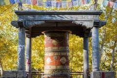 Het Tibetaanse Gebedwiel en geel doorbladert Stock Foto