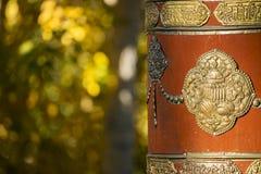 Het Tibetaanse Gebedwiel en geel doorbladert Stock Foto's