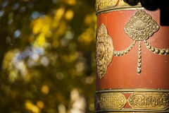 Het Tibetaanse Gebedwiel en geel doorbladert Royalty-vrije Stock Afbeeldingen