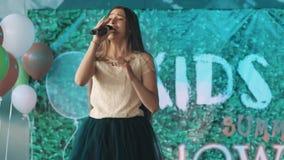 Het tiener mooie meisje in kleding het zingen in microfone bij toont stock video