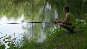 Het tienerkind vangt een hengel op de vijver stock footage