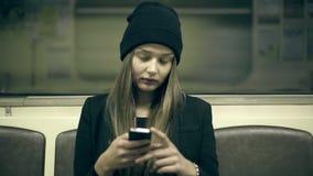 Het tienermeisje berijdt metro bij nacht en gebruikte smartphone stock videobeelden